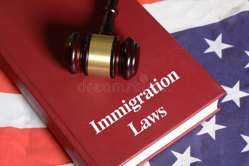 移民与惊堂木的法律书籍在美国旗子 免版税库存图片