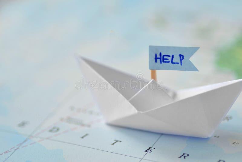 移民和请求收容所概念-在地图的纸小船 免版税库存照片
