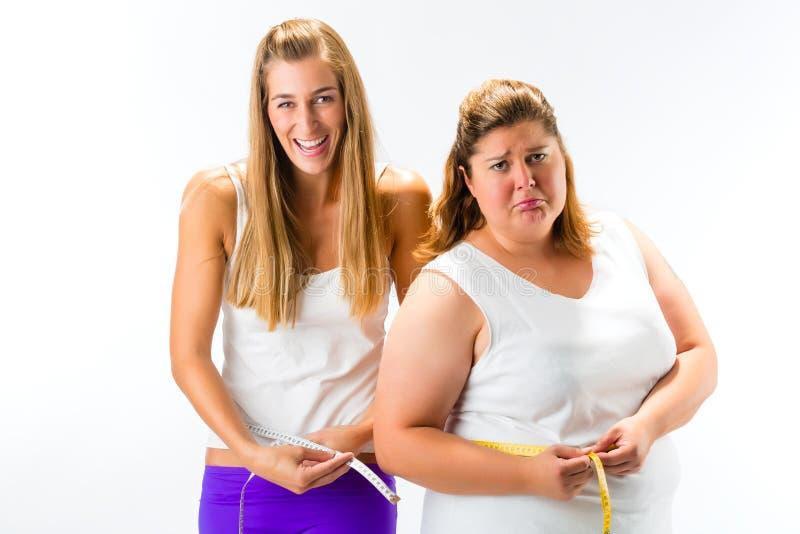 稀薄和肥胖有磁带的妇女测量的腰部 免版税库存照片
