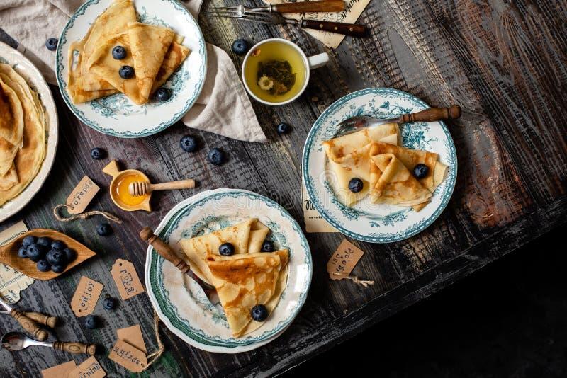 稀薄的美味的绉纱用蜂蜜,在三块葡萄酒板材的蓝莓顶上的射击  免版税库存图片
