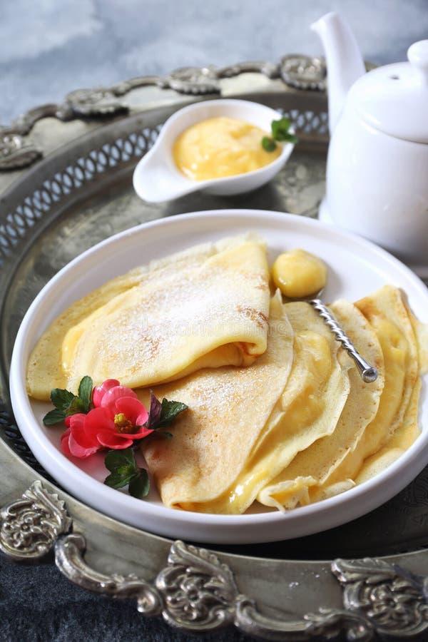 稀薄的苏打水薄煎饼俄式薄煎饼用柠檬酱和茶壶 免版税库存图片