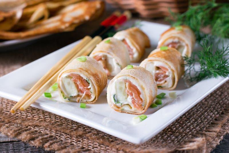 稀薄的薄煎饼劳斯用在板材的熏制鲑鱼和乳脂干酪 免版税图库摄影