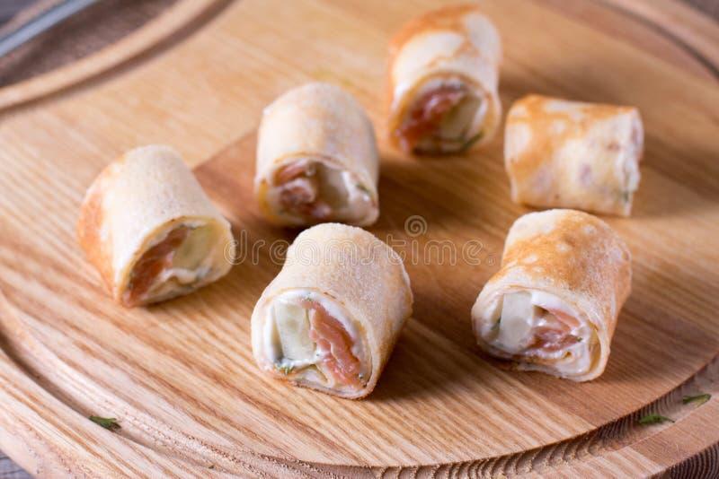 稀薄的薄煎饼劳斯用在板材的熏制鲑鱼和乳脂干酪 免版税库存照片