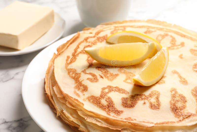 稀薄的薄煎饼服务用在板材特写镜头的柠檬 免版税库存照片