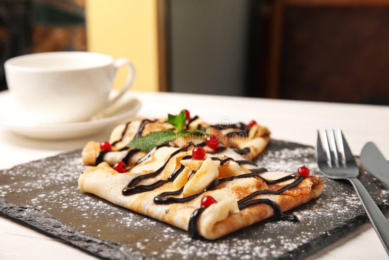 稀薄的薄煎饼服务用调味汁和莓果在板岩板材 库存图片