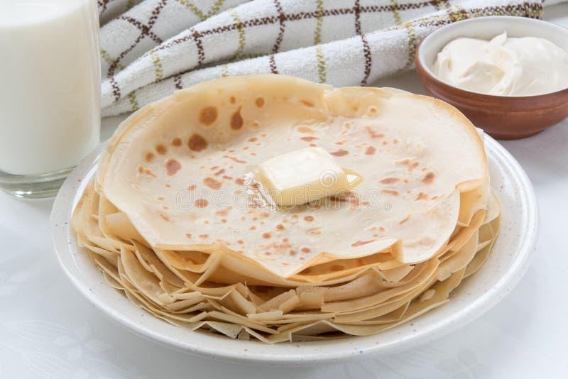 稀薄的薄煎饼用在白色板材的黄油 库存图片