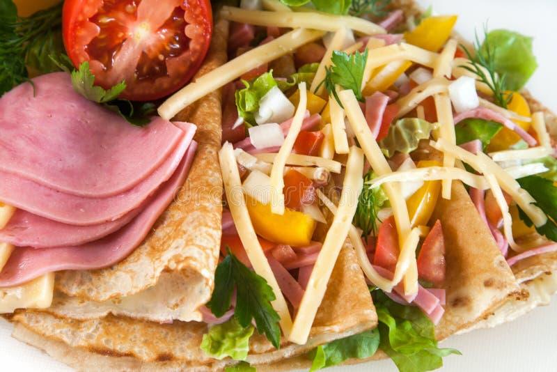 稀薄的薄煎饼用火腿、干酪和蔬菜 免版税库存图片