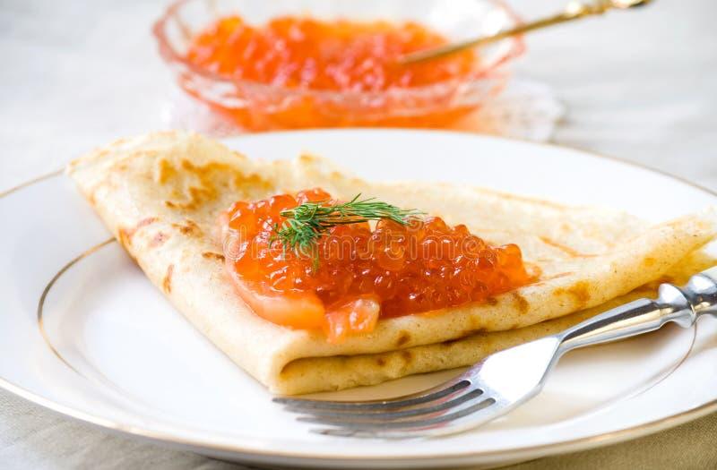 稀薄的薄煎饼用红色鱼子酱,三文鱼 免版税库存照片