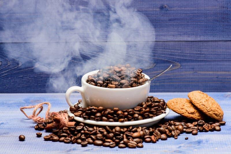 程度烤五谷 杯充分的咖啡棕色烤豆白色烟云蓝色木背景 咖啡馆饮料 库存照片