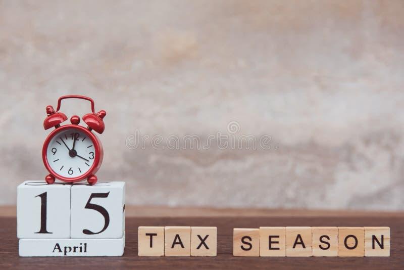 税与4月的15日季节天 与数字的日历木块立方体和在桌黑暗的板条木背景的红色闹钟 免版税库存图片