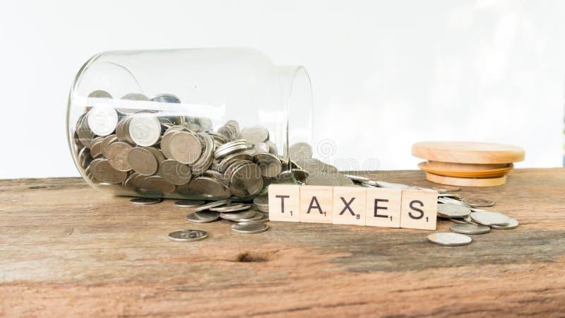 税在金钱硬币的木方形块打印文本 免版税库存图片