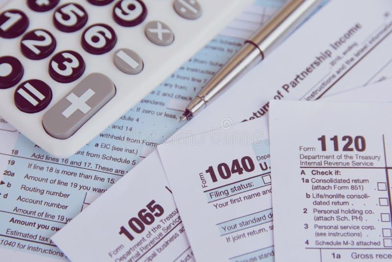 税季节 计算器,在美国报税表背景的笔 图库摄影