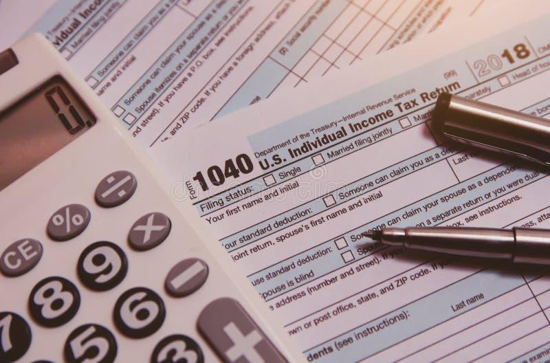 税季节 计算器,在1040报税表背景的笔 库存照片
