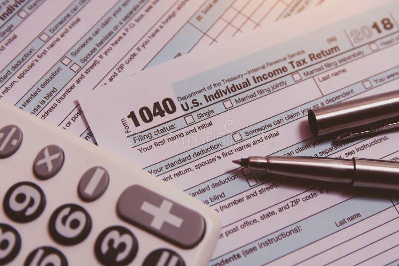 税季节 计算器,在1040报税表背景的笔 免版税库存图片