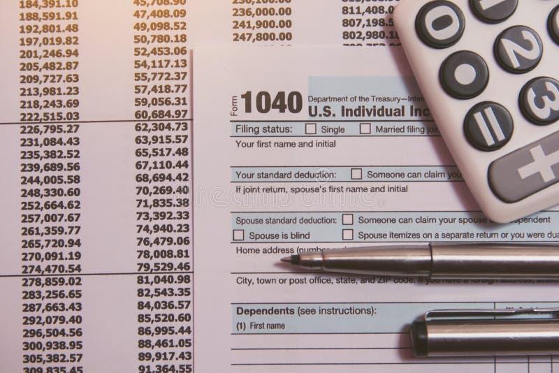 税季节 计算器,在1040报税表背景的笔 免版税库存照片