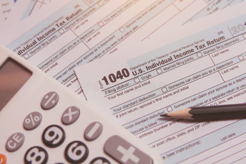 税季节 计算器,在1040报税表背景的铅笔 免版税库存图片