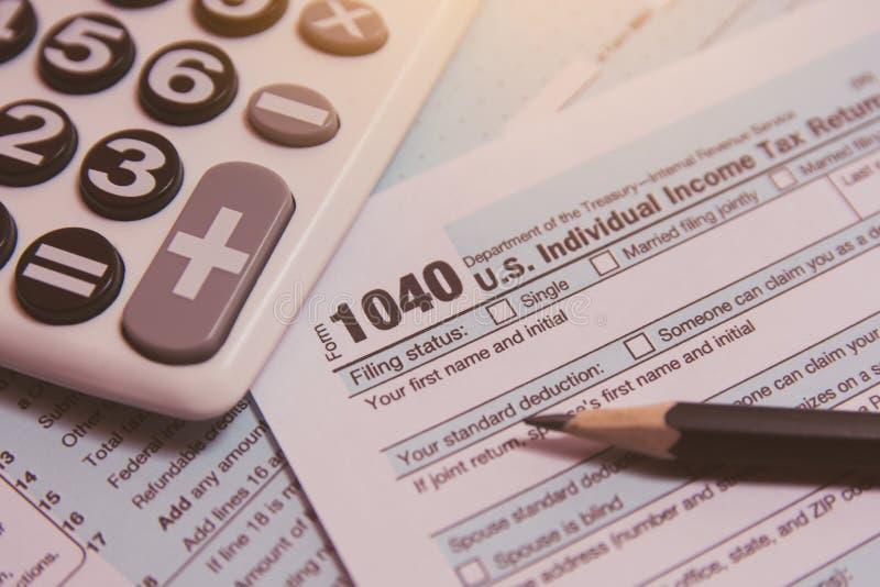 税季节 计算器,在1040报税表背景的铅笔 图库摄影