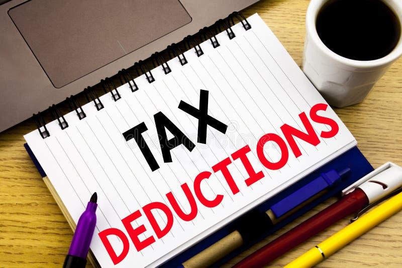 税收减免 在木背景的笔记本书写的财务接踵而来的税钱扣除的企业概念在 免版税库存图片