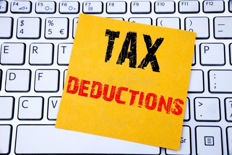 税收减免 在白色键盘backg的稠粘的便条纸写的财务接踵而来的税钱扣除的企业概念 免版税库存图片