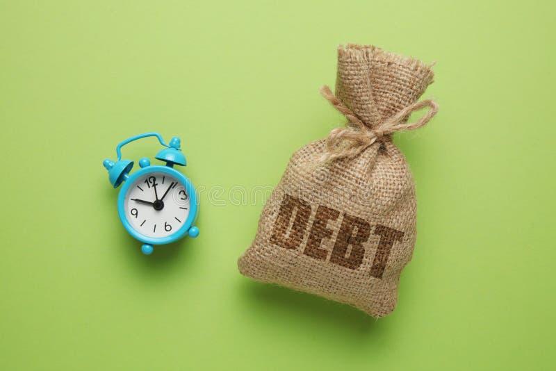 税款和利息在债务付款 过期付款,惩罚 与金钱和时钟的袋子在绿色背景 免版税库存图片