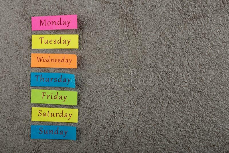 稠粘的笔记与几天在灰色水泥背景的星期 星期一,星期二,星期三,星期四,星期五,星期六和星期天 库存照片