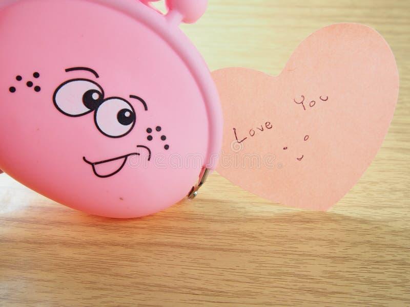 稠粘的纸笔记,爱您词,有微笑的面孔的桃红色钱包 免版税库存图片