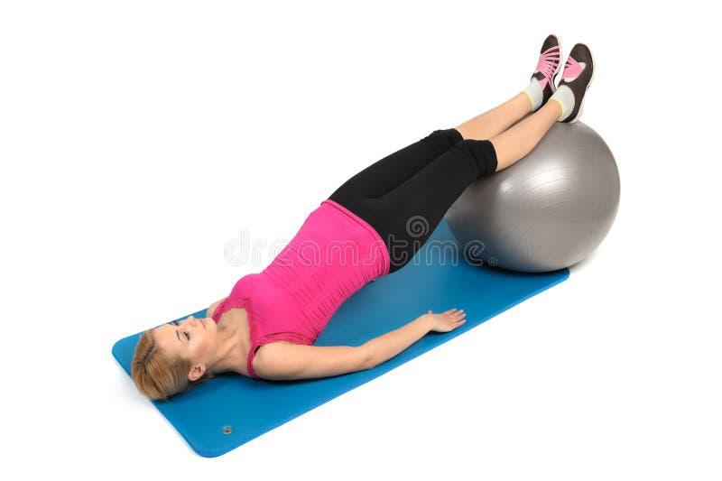 稳定健身球腿卷毛,女性靶垛锻炼 库存图片