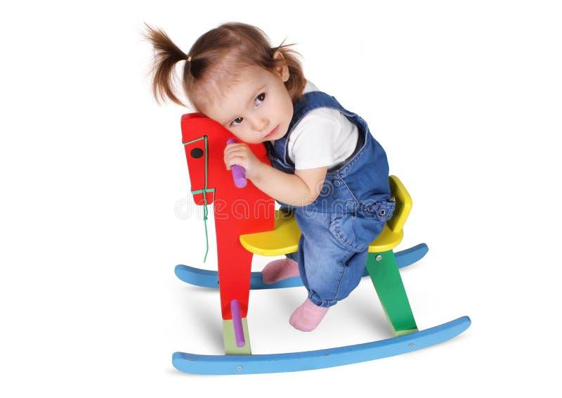 滑稽的体贴的孩子在玩具马作梦,隔绝在白色 免版税库存图片