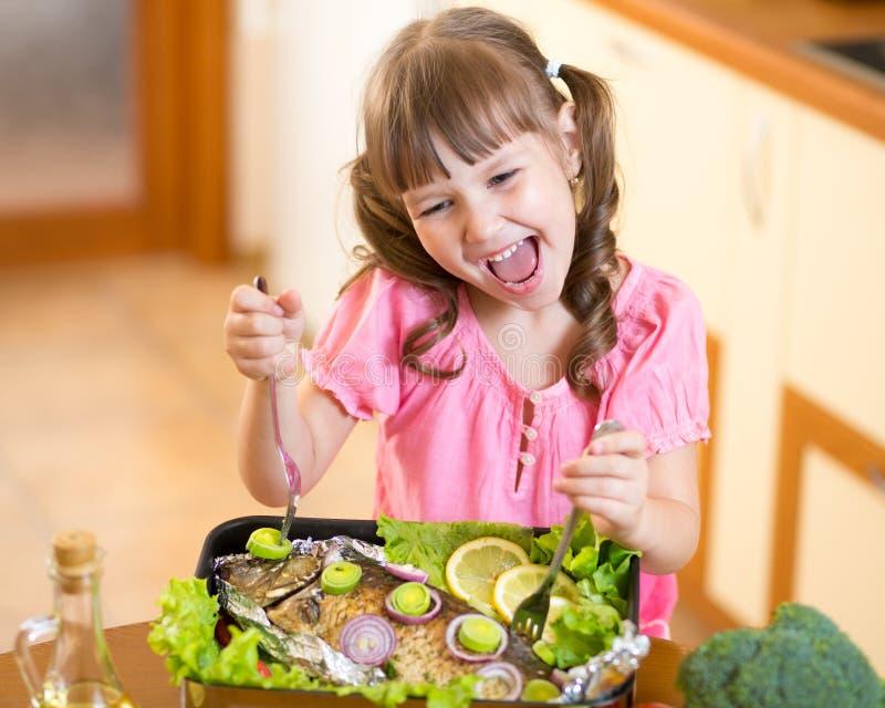 滑稽的儿童女孩和烤鱼 吃健康 免版税库存图片