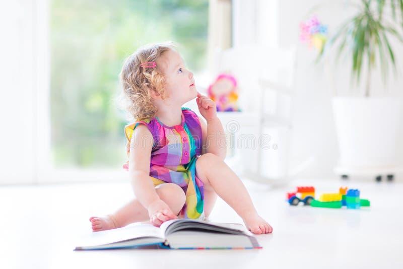 滑稽的卷曲小孩女孩阅读书坐地板 免版税库存照片