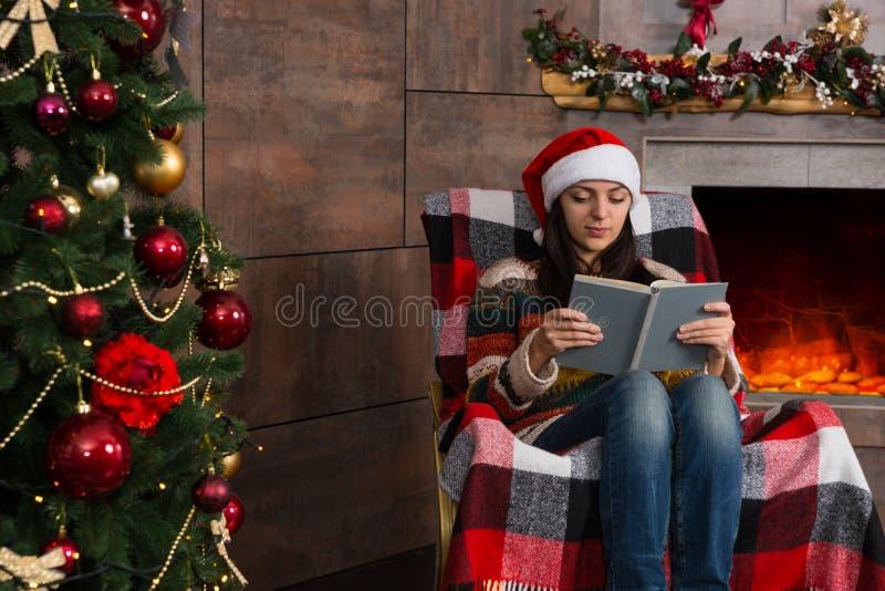 滑稽的圣诞节帽子读书的可爱的少妇,当sitt时 库存图片