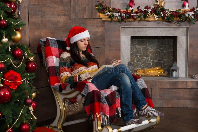 滑稽的圣诞节帽子读书的美丽的妇女,当参加时 库存图片
