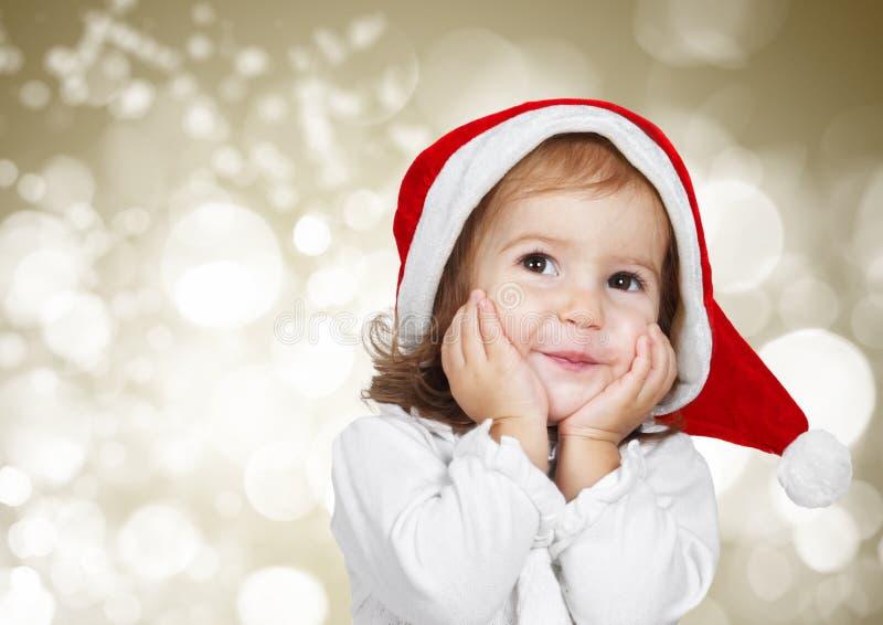 滑稽的孩子穿戴了圣诞老人帽子,在金黄bokeh背景 图库摄影