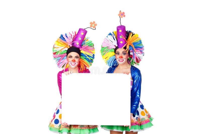 滑稽的小丑夫妇有一张空白的海报的 免版税库存图片