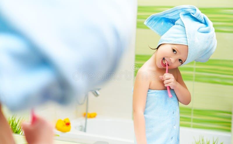 滑稽的小女孩清洗牙与牙刷在卫生间里 库存图片