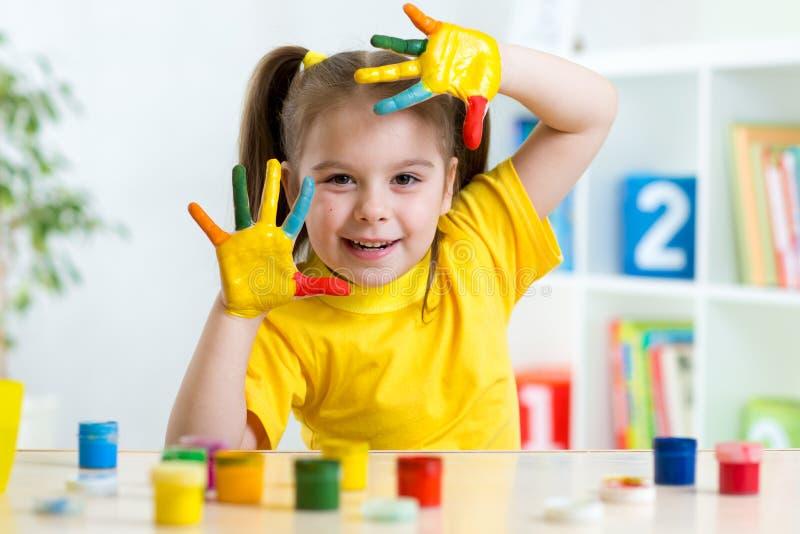 滑稽的小女孩用在五颜六色绘的手 免版税图库摄影