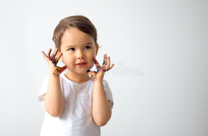 滑稽的小女孩用绘在五颜六色的油漆被隔绝的手 免版税库存照片