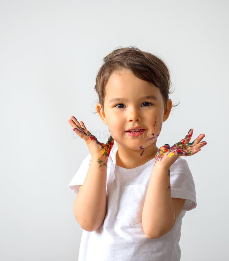 滑稽的小女孩用绘在五颜六色的油漆被隔绝的手 库存图片
