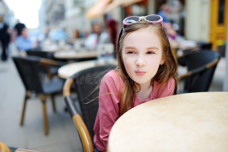 滑稽的小女孩获得乐趣在一个室外咖啡馆 免版税库存照片