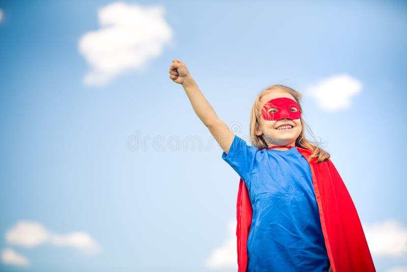 滑稽的小女孩plaing的力量特级英雄 免版税库存照片