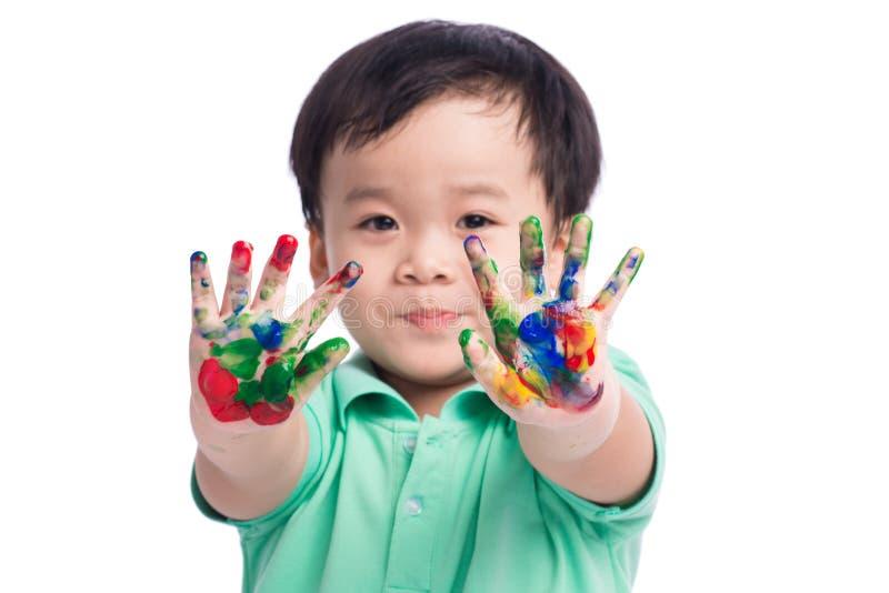 滑稽的小男孩用在五颜六色的油漆绘的手 背景查出的白色 库存图片