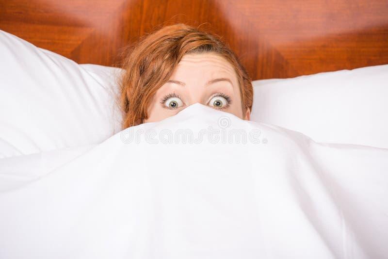 滑稽的少妇在看和偷看在板料的床上惊奇 免版税库存照片