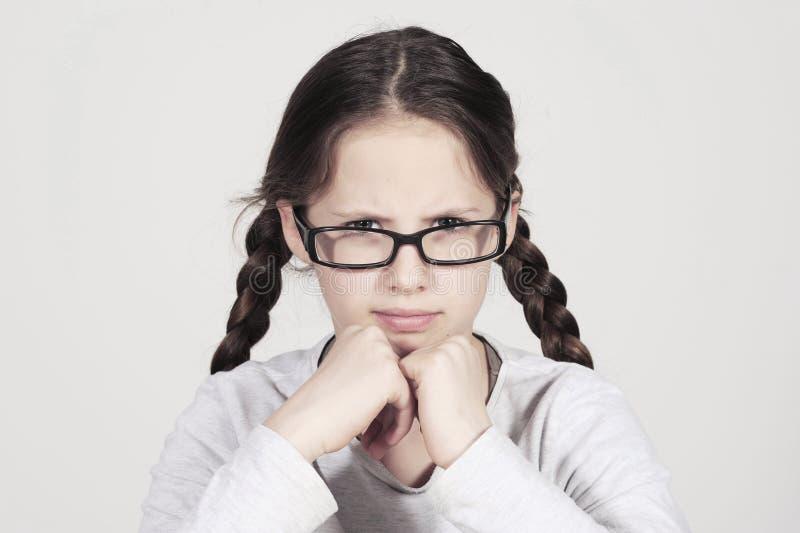 滑稽的少年女孩看起来恼怒在她的眼镜后 免版税库存图片