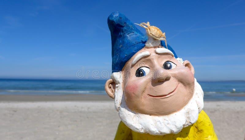滑稽的庭院地精的画象在海滩前面的 库存照片