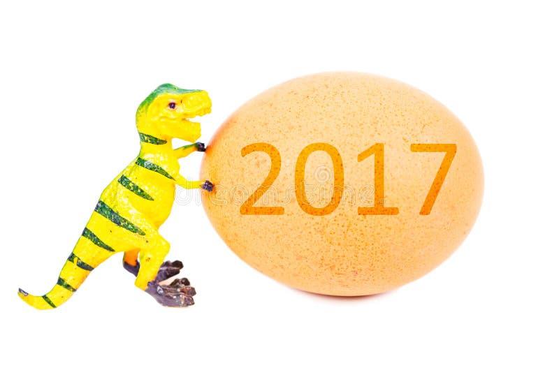滑稽的彩色塑泥恐龙玩具和鸡蛋与2017年 免版税库存照片