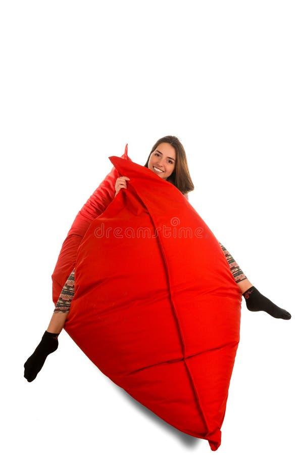 滑稽的微笑的少妇坐红色装豆子小布袋沙发椅子isol 库存图片
