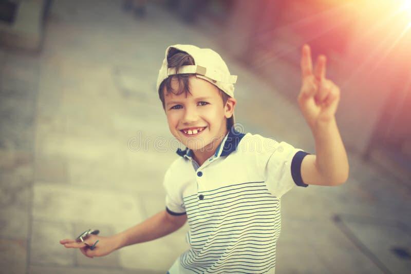 滑稽的愉快的矮小的白种人男小学生在盖帽的夏天 免版税库存照片