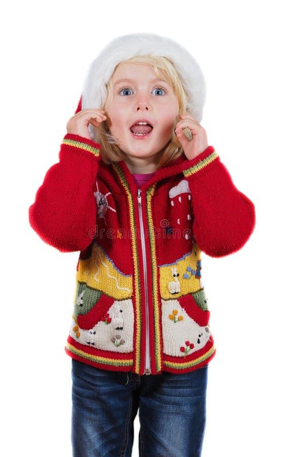 滑稽的有圣诞老人帽子的圣诞节小女孩 库存照片
