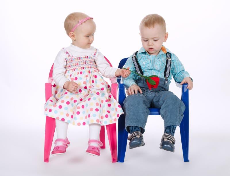 滑稽的男孩和女孩坐在白色的椅子 库存照片