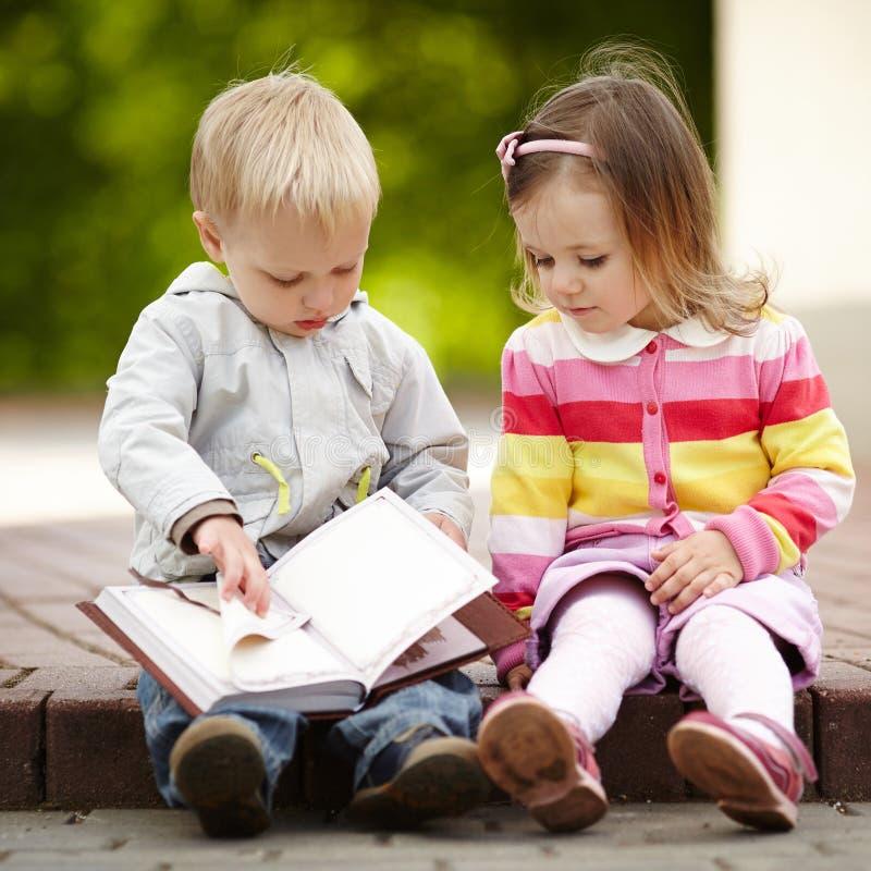 滑稽的男孩和女孩阅读书 库存照片